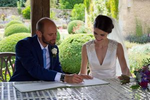 groom signing the register with bride looking on