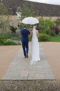 bride and groom under a white umbrella walking away