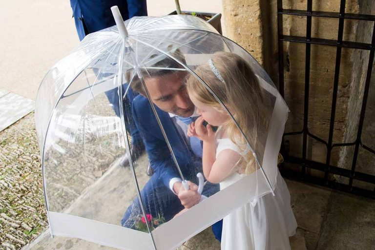 Father and daughter under an transparent umbrella