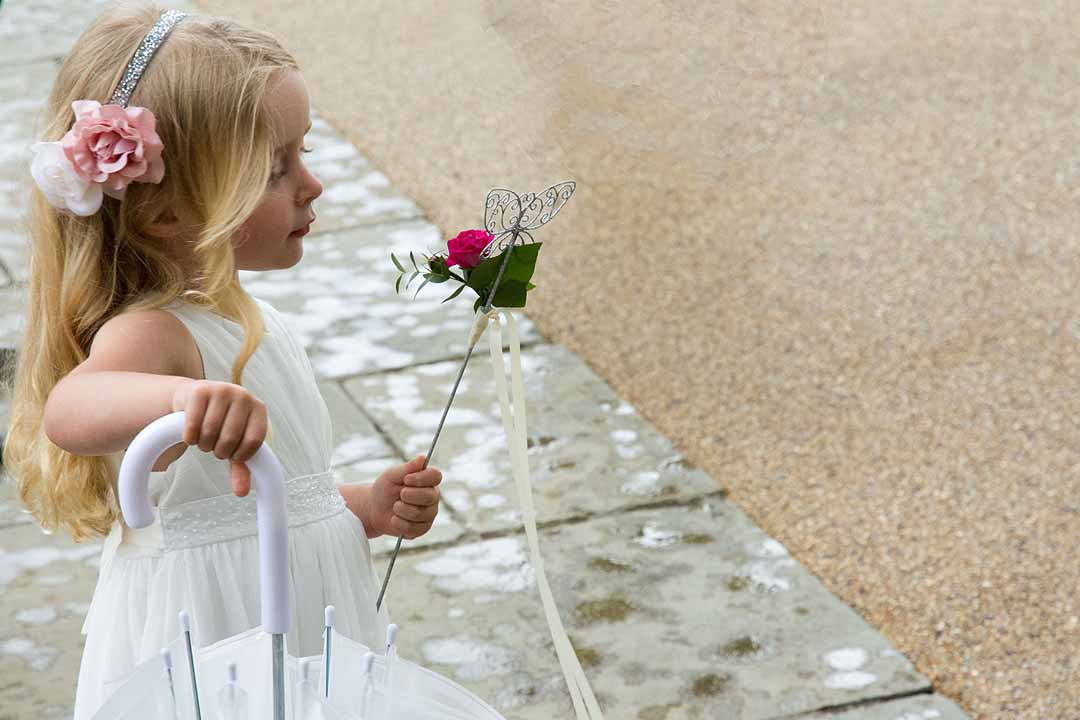 Flowergirl in white dress with pink accessories and umbrella