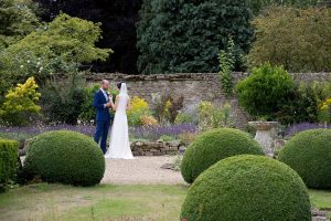 Bride and groom in gardens at Caswell House, Cotswolds
