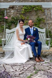 Bride and groom sitting on a swing bench
