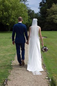 Bride and groom walking down a garden path