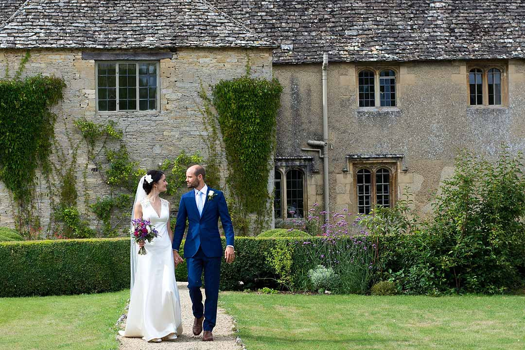 Bride and groom looking at each other as they walk through a garden