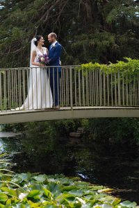Bride and groom on bridge at Caswell House, Cotswolds