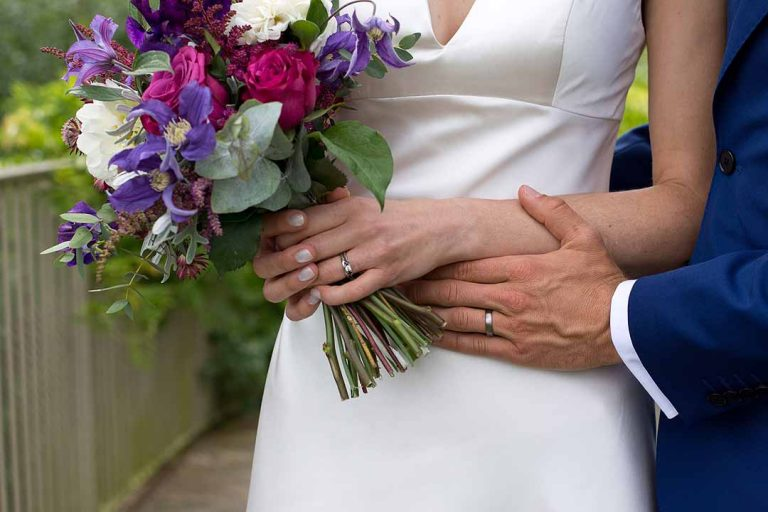Groom and bride holding pink and purple bouquet
