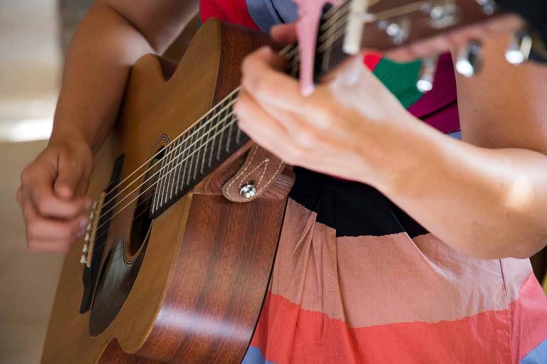 Lady playing guitar in a colourful striped dress