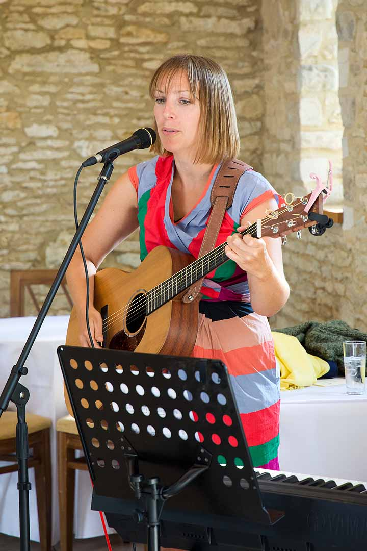 Lady playing a guitar and singing, wearing a colourful striped dress