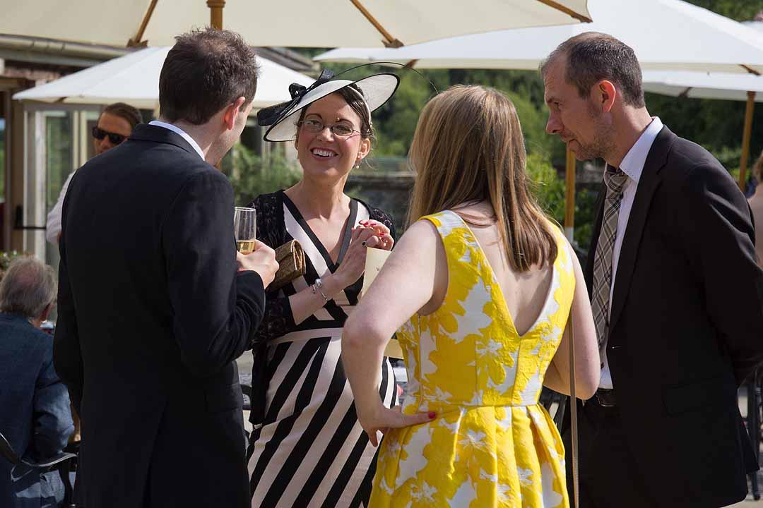 Wedding guests chatting under white umbrellas