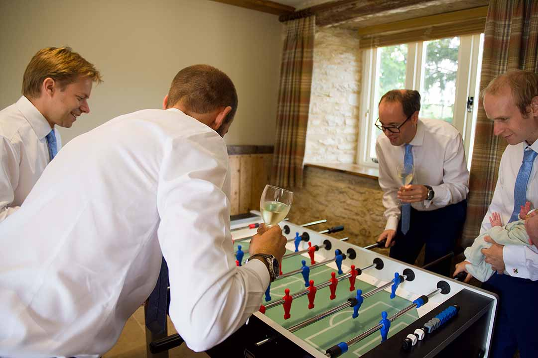 four men and a baby playing subbuteo