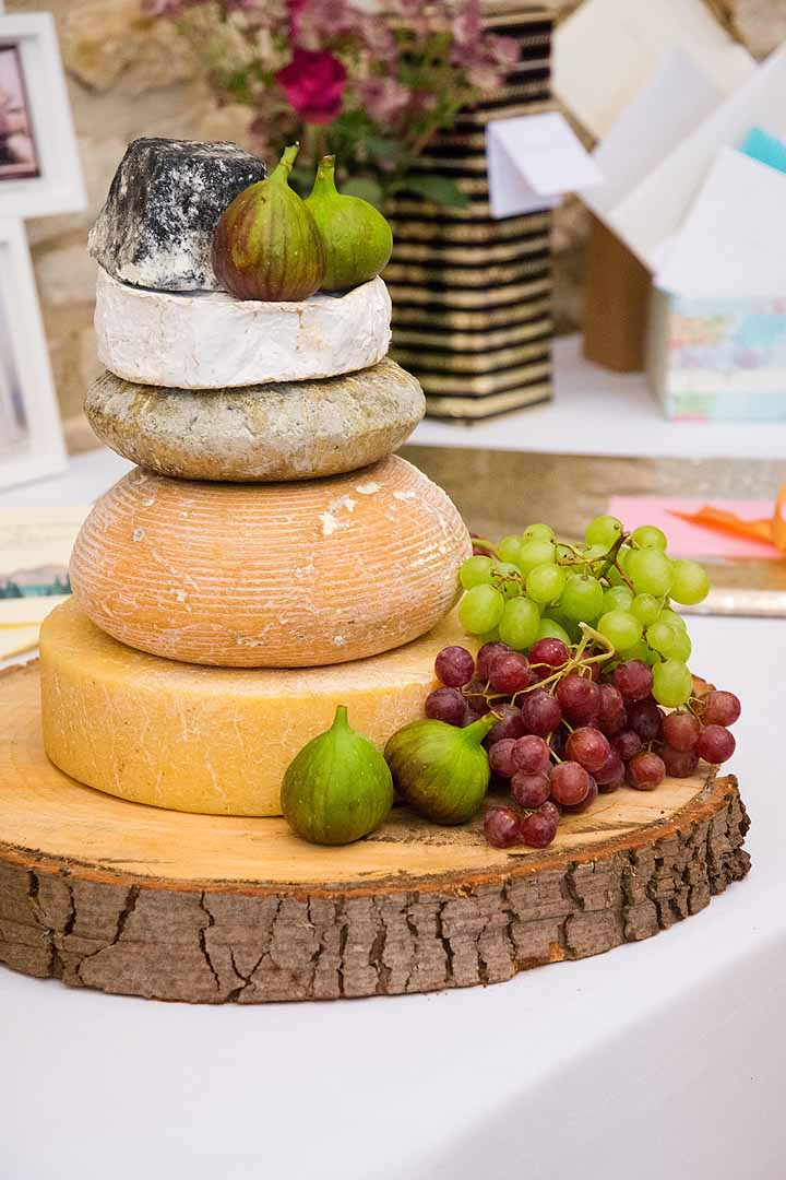 Stack of cheeses with grapes and figs