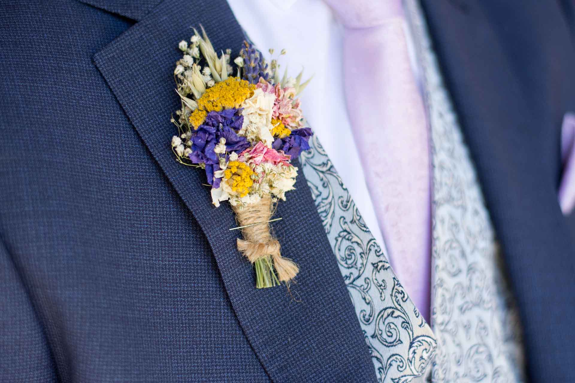 dried flower button hole on blue suit